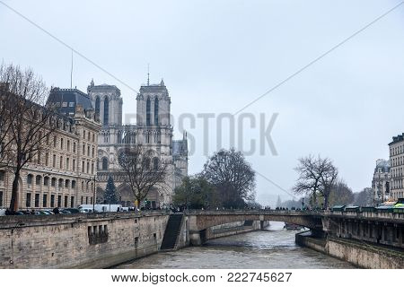 PARIS, FRANCE - DECEMBER 20, 2017:  Notre Dame de Paris Cathedral taken from the Seine river with the Double bridge (pont du Double) in front during a grey cloudy winter afternoon