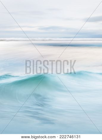 A soft focus, long exposure of flowing Pacific ocean waves and surf on an overcast day.