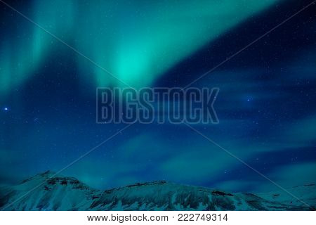 Amazing view on the Northern light over high mountains covering with snow, forces of nature, Aurora Borealis, Iceland