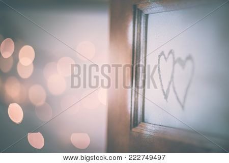 Open doors to love, two handwriting hearts on the open door, festive blurry bokeh lights behind, conceptual photo of first affection or true love