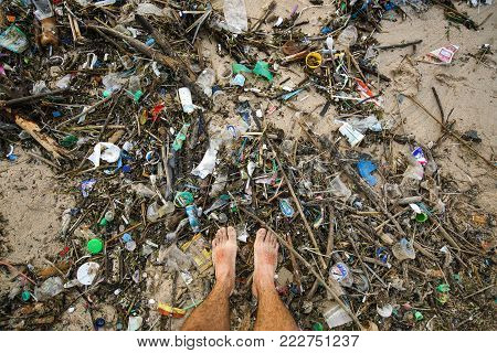 Indonesia, Bali, January 19. 2017: The legs of a man barefoot standing in the garbage on the sandy ocean beach. Recycling concept. The problem of ecology, environmental pollution.