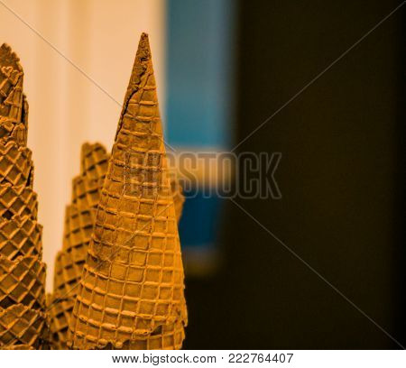 Closeup of stack of chocolate ice cream cones with point of cone pointed toward ceiling