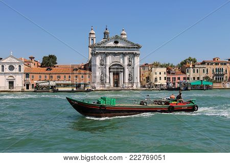 Venice, Italy - August 13, 2016: Service boat with people opposite the Church of Santa Maria del Rosario (Gesuati). View from Giudecca Canal