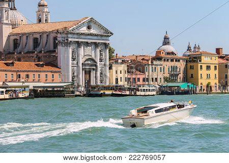 Venice, Italy - August 13, 2016: Tourist boats opposite the Church of Santa Maria del Rosario (Gesuati). View from Giudecca Canal