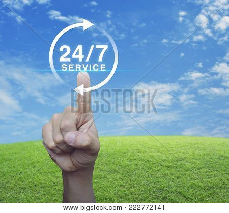 Hand pressing button 24 hours service icon over green grass field with blue sky, Full time service concept
