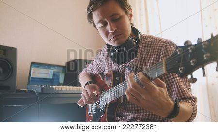Young attractive male musician composes and records soundtrack playing the guitar, using computer, focus on face and hands, close-up