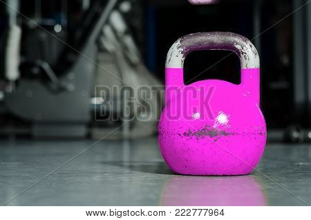 Pink or purple kettlebell weight on the gym floor ready for female strength and conditioning fitness training