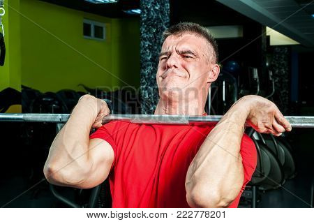 Strong muscular man with muscles performing weightlifting training sport with heavy metal barbell weight and hard face expression