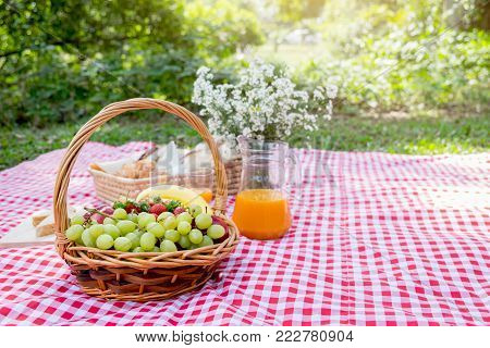 Healthy food and accessories outdoor summer or spring picnic, Picnic wicker basket with fresh fruit, bread and a glass of refreshing orange juice in the camping nature background.