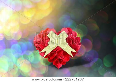 Rose petals heart shape with golden gift bow on background bokeh