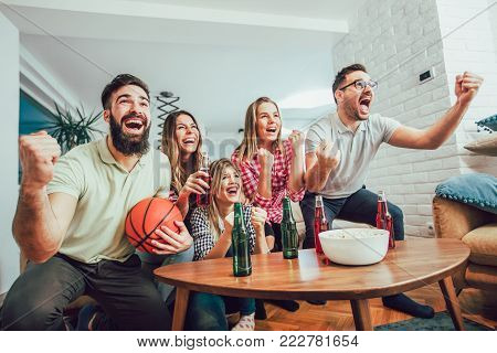 Happy friends or basketball fans watching basketball game on tv and celebrating victory at home.Friendship, sports and entertainment concept.