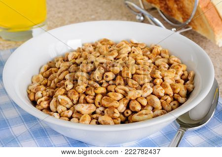 Honey coated puffed wheat breakfast cereal in a breakfast setting with toast and juice