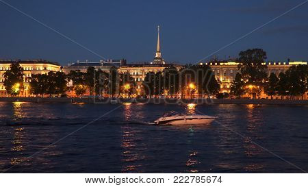 Night illumination of the Neva coast in St. Petersburg. A motor boat sails along the river poster