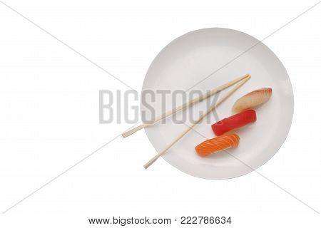 Isolated plate with sushi on the white background. Sushi with tuna, salmon, redfish and chopsticks. Plate with place for text. Japan cuisine.