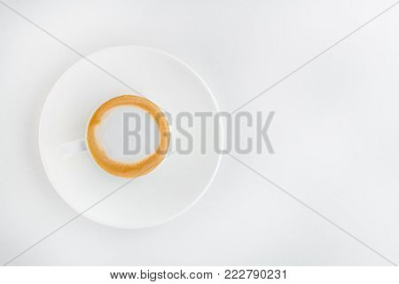 cup of coffee with foam on a plate on a white background.