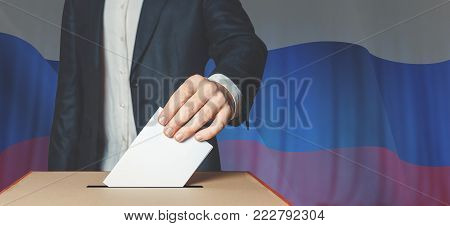 Man Voter Putting Ballot Into Voting box. Democracy Freedom Concept On Flag Background