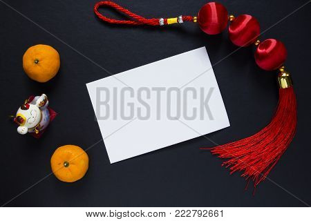 Chinese New Year knot and tangerines on black background with blank postcard. Lunar New Year decor top view photo. Maneki neko cat. Asian winter holiday greeting card flat lay. New Year card mockup