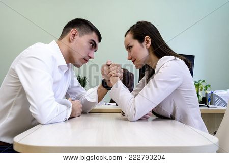 Man And Woman In Office Clothes Wrestling On Hand At The Desk In The Office.