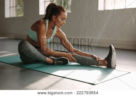 Fitness woman smiling while resting on exercising mat at gym. Female sitting on exercise mat and smiling after training.
