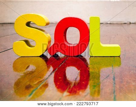 the acronym SQL on a wooden floor with reflection