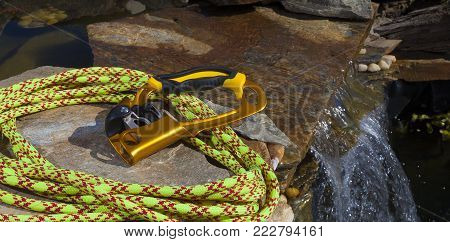 Climbing rope and an ascender on a rock near a small waterfall