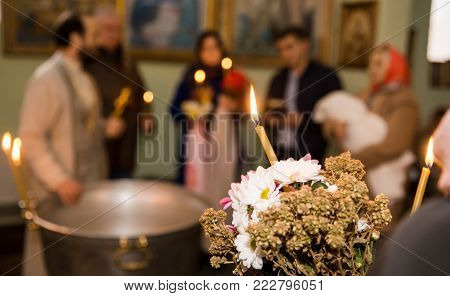 The rite of infant baptism in the church, flowers and lighted candles