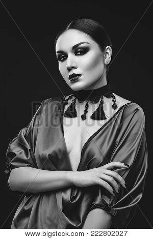 closeup portrait of beautiful young woman with balck hair and dark smokey eye makeup wearing silk blouse. hands with purple nail polish. studio beauty shot. copy space.