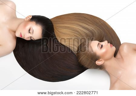 two beautiful young women with healthy shiny straight hair. blonde and brunette lying on white floor. studio beauty shot copy space.