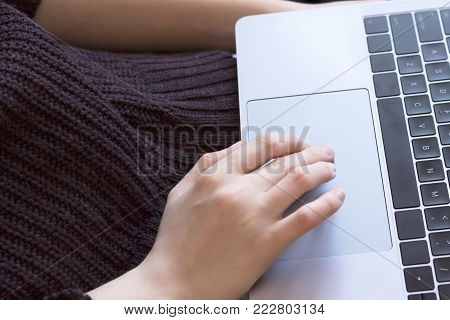 Female hand presses the touchpad. Concept freelancing, information search, social networks.