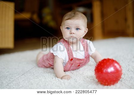 Cute baby playing with red gum ball. Lttle girl looking at the camera and crawling. Family, new life, childhood, beginning concept. Baby learning grab