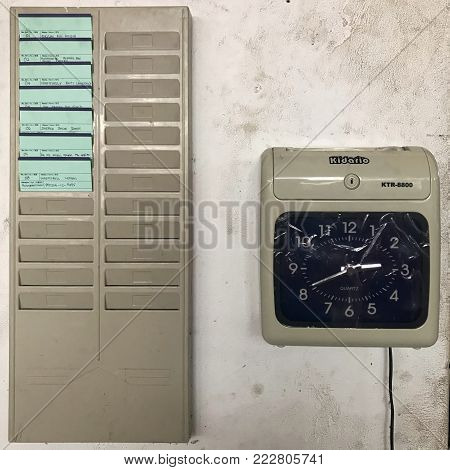 Sabah, MALAYSIA - 17 December 2017: A punch card machine and shelf attached on the wall in a car workshop.