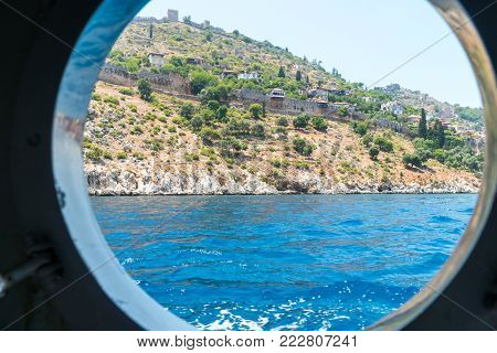 The view from the window of a marine vessel on the stone walls of the old coastal fortress of Alanya. View of sparse mountain vegetation and a small dwelling houses