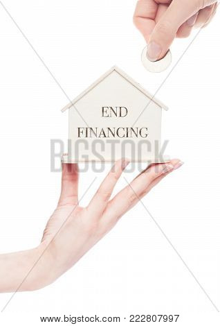 Female hand holds wooden house model and hand holding the coin with conceptual text. End Financing
