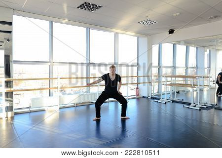 Medical student in sportswear rehearse dance on parquet floor in hall, barefoot boy hopping rhythmically moving hands supplying hair. Male with good body wearing black V-neck and trousers. Concept of choreographic school, sport clothes for men or well-equ