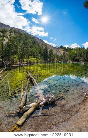 High altitude blue lake in idyllic uncontaminated environment with clean and transparent water. Summer adventure in the Italian French Alps. Wide angle view.