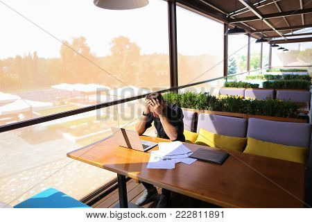 Freelance copywriter typing text fast on laptop keyboard at cafe table and looking tired. Handsome young man dressed in black shirt has dark hair and beard. Concept of typewriting skills and independent contractor for agencies.