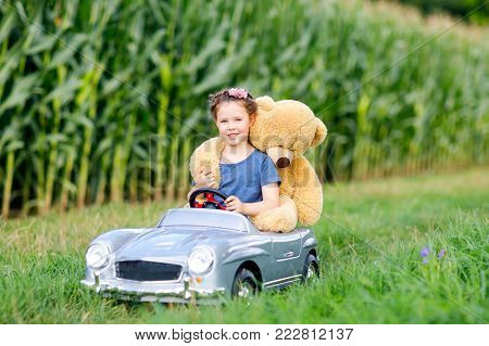 Adorable little kid girl sitting in big vintage old toy car and having fun with playing with big plush toy bear, outdoors. Child enjoying warm summer day in nature landscape. Girl driving car.