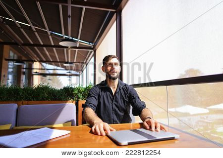European translator sorting papers and closing laptop lid at cafe. Young persistent man dressed in black shirt looks happy and successful. Concept of finishing work and resting.