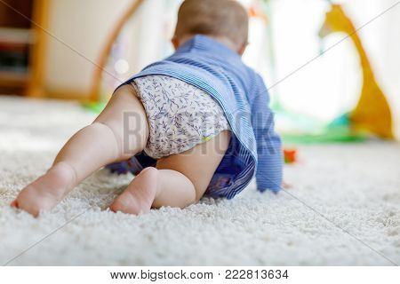 Little cute baby girl learning to crawl. Healthy child crawling in kids room with colorful toys. Back view of baby legs. Cute toddler discovering home and learning different skills.