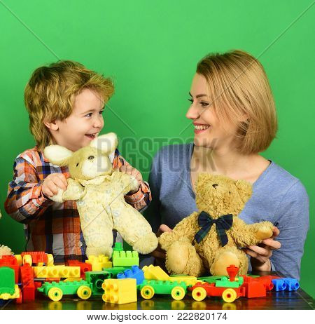 Woman and boy play on green background. Childhood and playing concept. Family with happy faces hold teddy bears near colored construction blocks. Mom and kid in playroom.