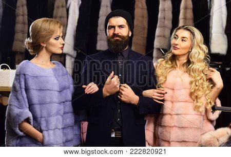 Women In Violet And Pink Fur Coats With Shop Assistant.