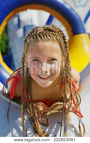 An enthusiastic girl on an inflatable attraction. Joy and fun during the holidays