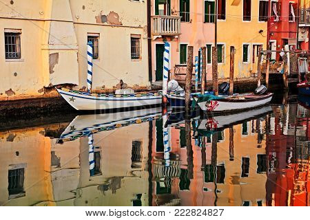 Chioggia, Venice, Italy - September 8, 2017: waterway in the old town with colored houses, mirror on the water and wooden fishing boats. Photo taken on September 8, 2017 in Chioggia, Venice, Italy
