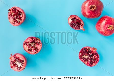 Pomegranates whole and cut into halves and quarters on blue background with copy space. Top view.