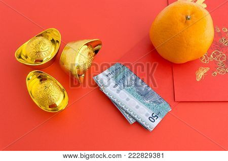 Chinese New Year Background 50 Ringgit Malaysia in Red Envelope with Mandarin Orange and gold ingots with Chinese Character Happiness and Prosperity on red background