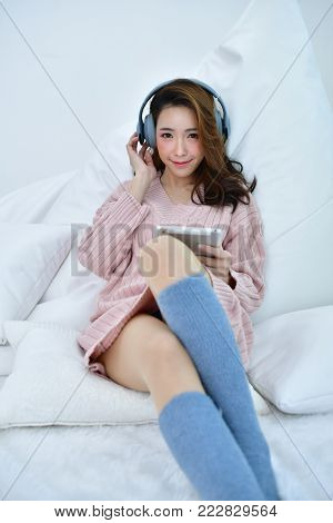 Winter Concept. Cute Asian girl in winter dress. Beautiful woman is relaxing in a white bedroom. Beautiful women in winter clothes are listening to music in the bedroom. Woman wearing a sweater in a white bedroom.