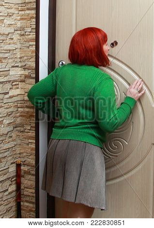The girl closes the door from the inside of his apartment. She stands back , holding the door handle and looks through the peephole.