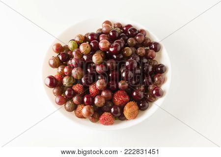 Assorted fresh garden berries in a white plate