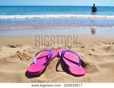 pink flip flops at a greek beach - greek summer destination