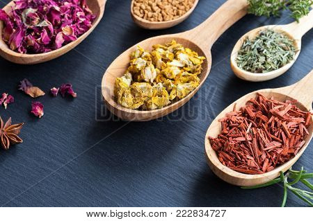 Herbs on wooden spoons on a dark background with copy space. Sandalwood, horsetail, mullein (velvet plant), fenugreek seeds, rose petals.
